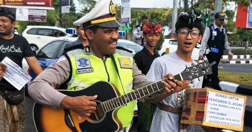 Bapak Polisi ini ikut ngamen untuk membantu para pengungsi Gunung Agung